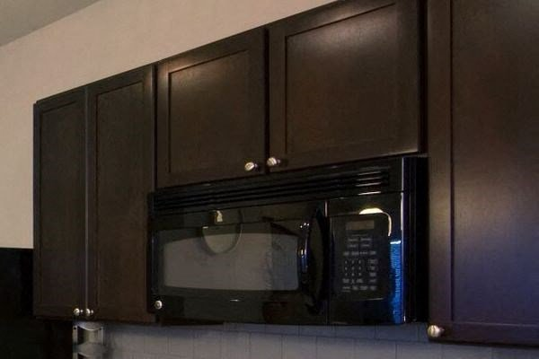 dark wood cabinets in kitchen with built in microwave