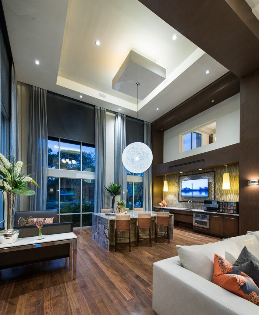 Resident lounge with plank wood flooring and floor-to-ceiling windows. Soft and hard seating with tables and chairs. Partial kitchen and coffee bar with TV.