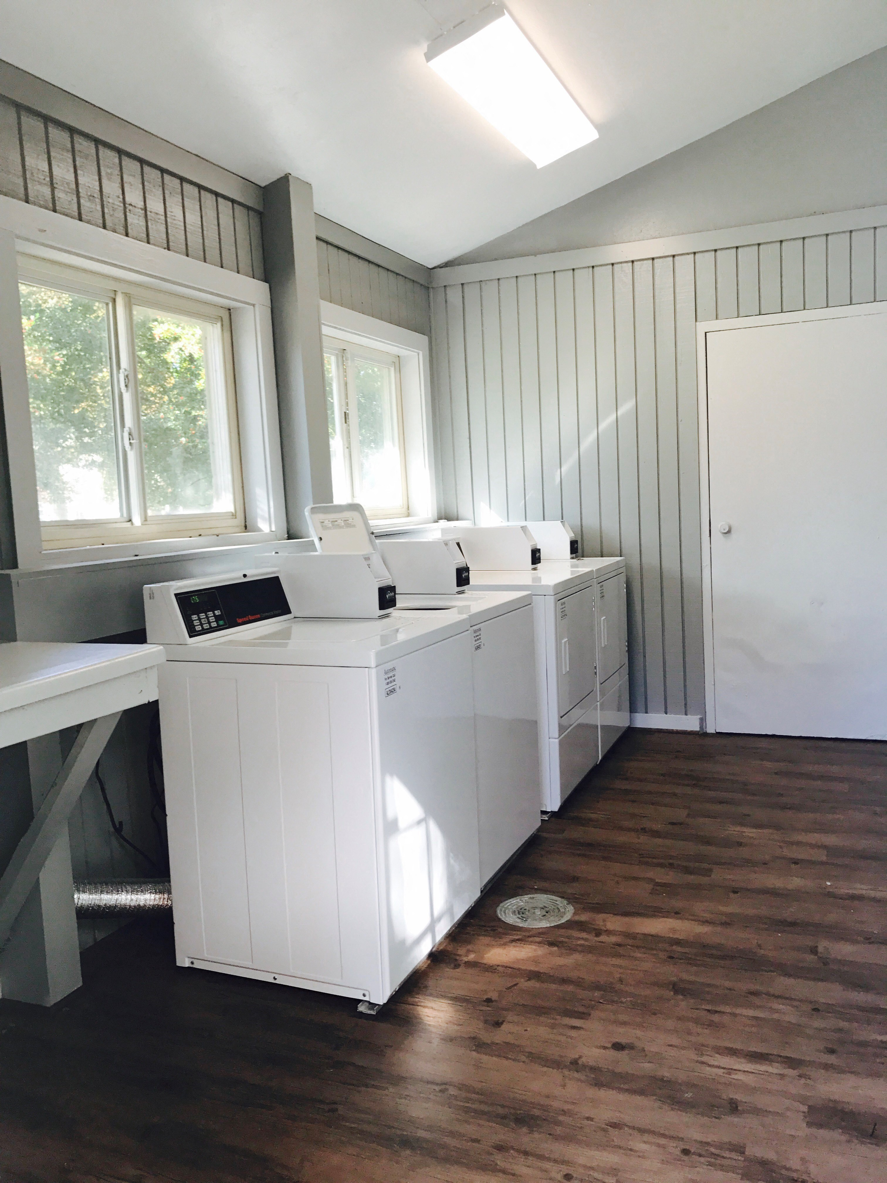 A laundry room featuring white washers and dryers, wooden floors, and grey walls