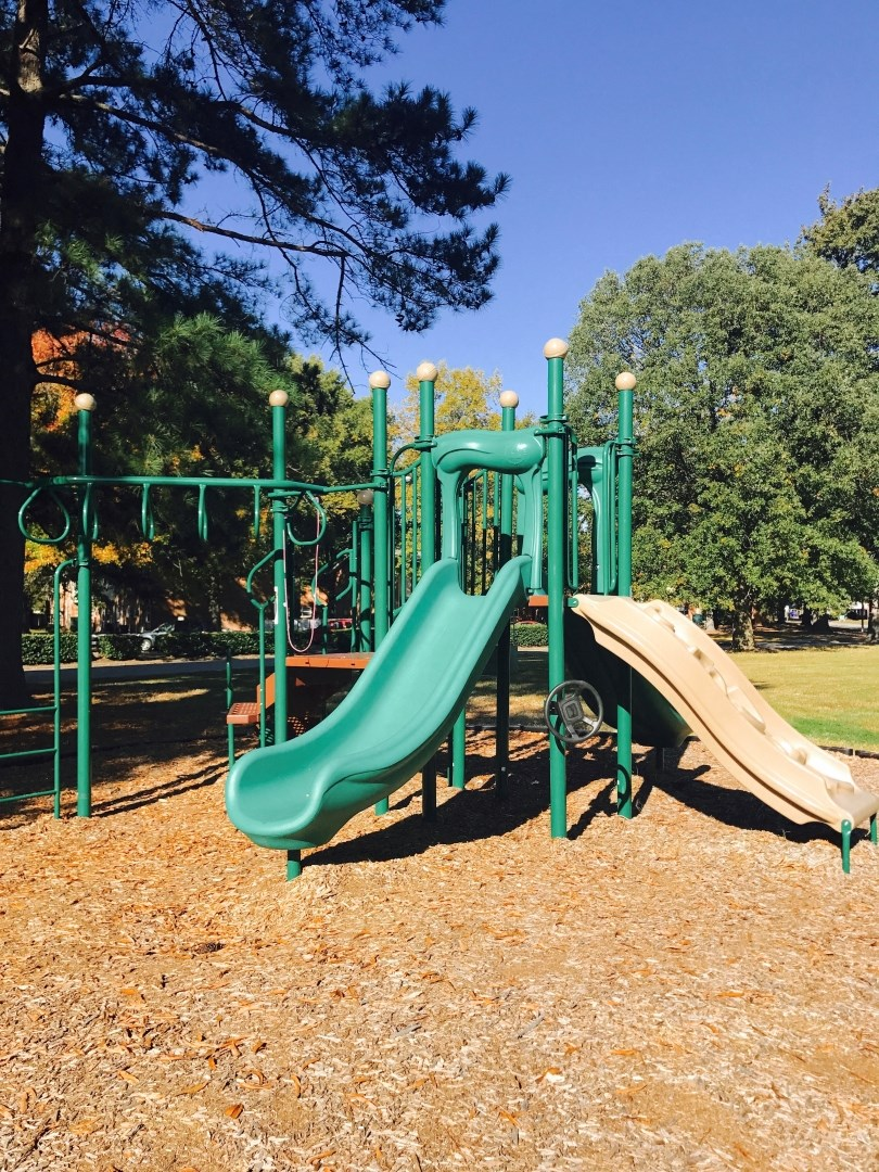 playground with a green slide and jungle gym surrounded by tall trees and wood chips