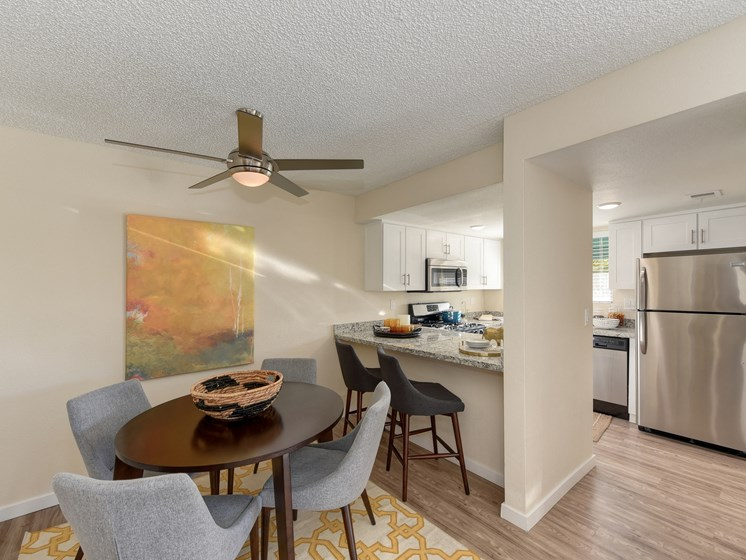 Luxury Apartment Community Dining Area and Kitchen with Bar Seating and Stainless Steel Appliances
