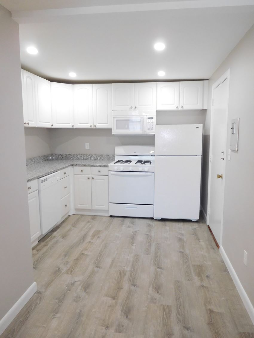 Renovated kitchen with granite counters, white cabinets and white appliances