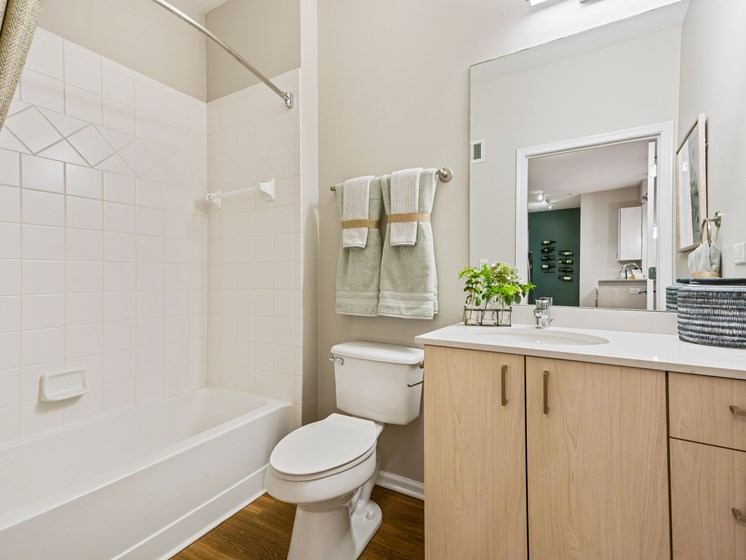 Bathroom with full tub, shower, tiling, and modern cabinetry