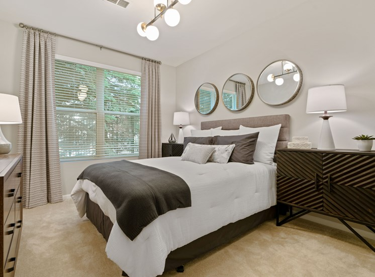 Bedroom with queen size bed, grey accents, 3 mirrors, carpeting, large nightstand, and window