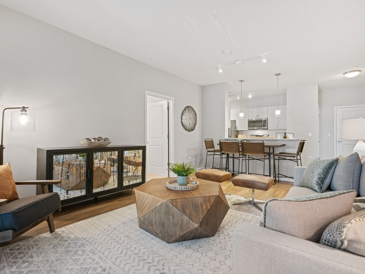 Living room view of dining set, geometric coffee table, mirrored cabinetry, and seating