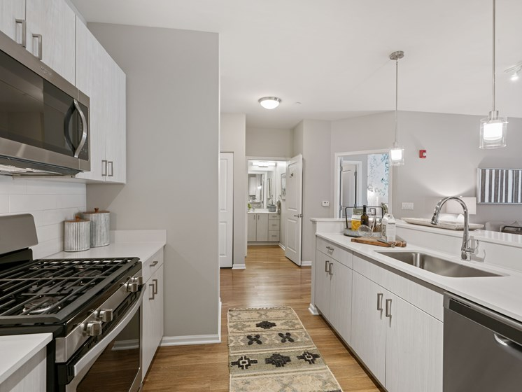Kitchen view of living area, and view into bathroom, with a stainless steel dishwasher, stove, and microwave in the view