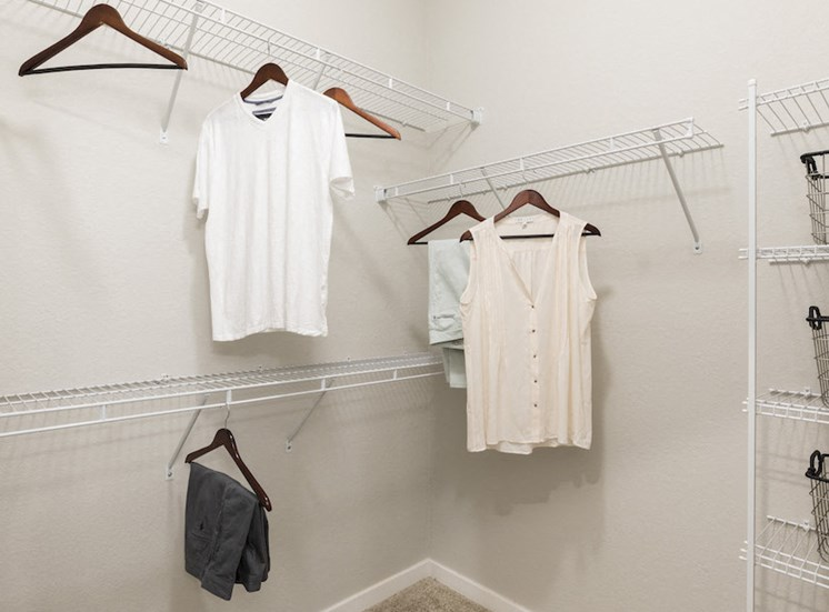 large closet with shelving and hanging clothes
