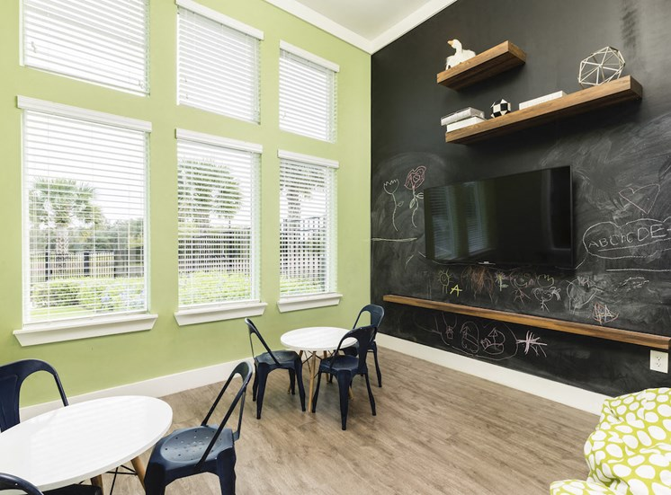 fitness center child room with tables chairs and blackboard