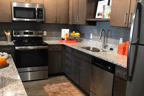 galley kitchen with modern stainless steel appliances