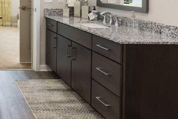 dark wood cabinet in bathroom with granite countertops