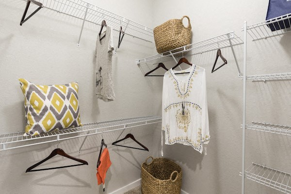 large closet with built in shelving and example hanging clothes