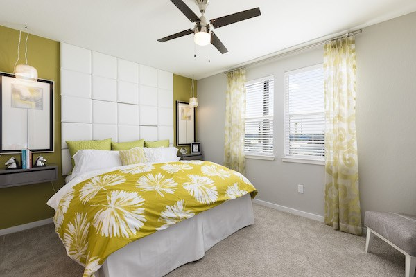 furnished bedroom with large large windows and ceiling fan