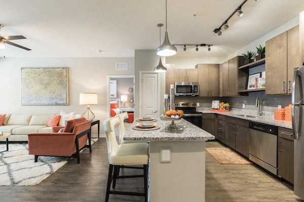 open concept kitchen with granite countertops and pendant lighting