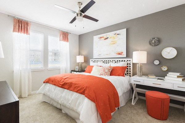 model apartment bedroom with large windows and modern fan