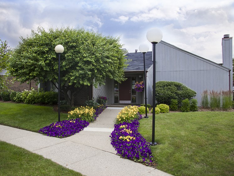 Building Exterior and Entrance Walkway with Flowerbeds at Three Oaks Apartments, MI