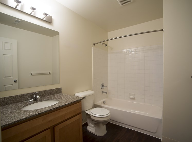 Bathroom with granite countertops and ceramic tub surround at Woodland Villa Apartments, Michigan