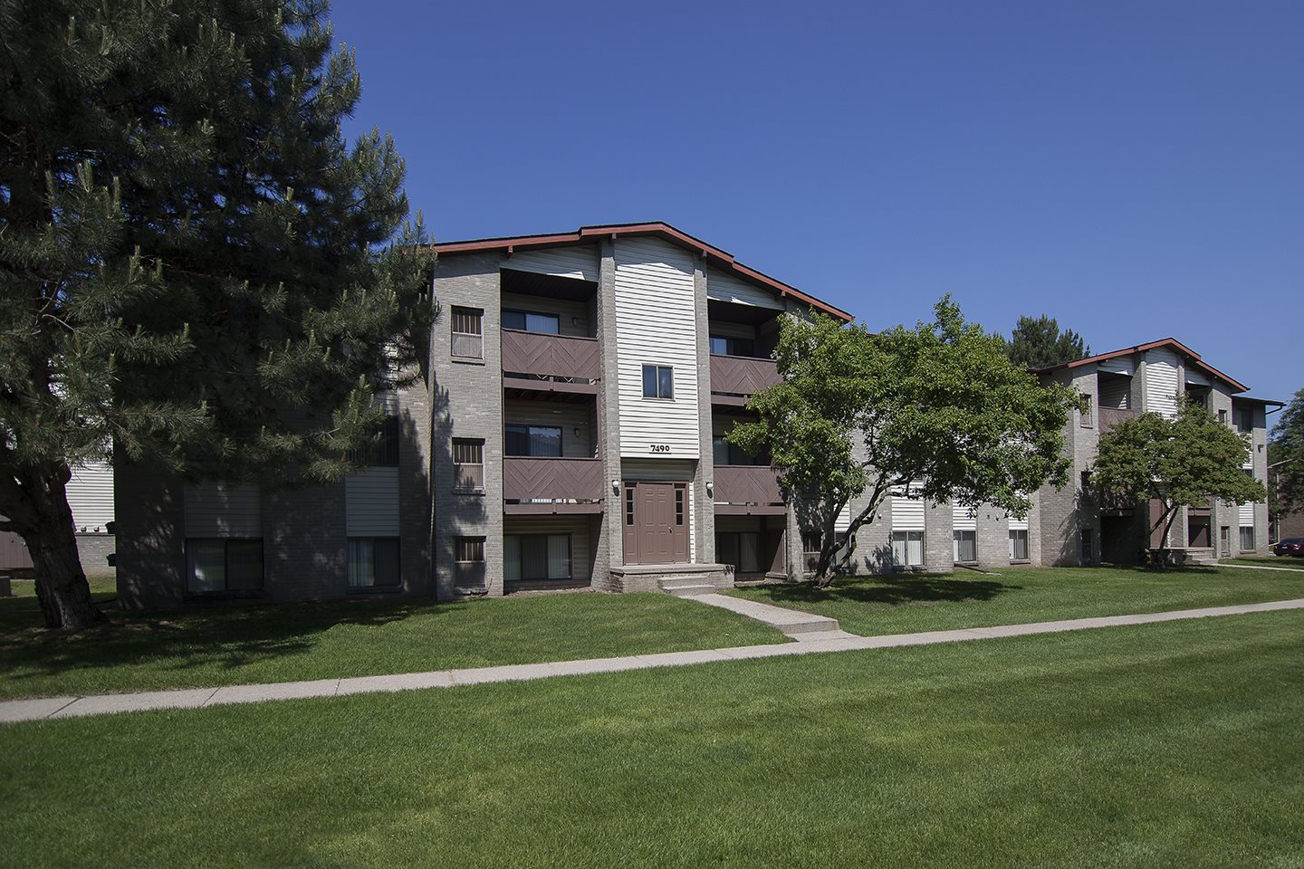 Three story apartment building exterior at Woodland Villa Apartments in Westland