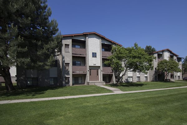 Three story apartment building exterior at Woodland Villa Apartments in Westland