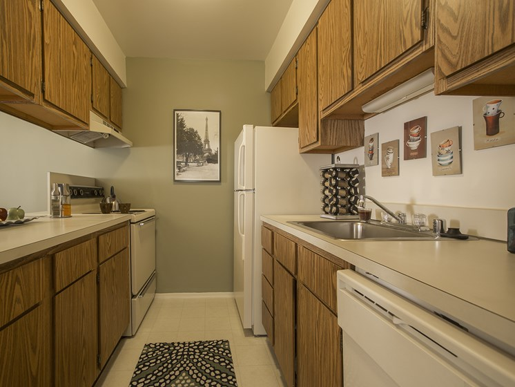 Kitchen with all appliances included (refrigerator, stove, dishwasher and garbage disposal) at Woodland Villa Apartments in Westland