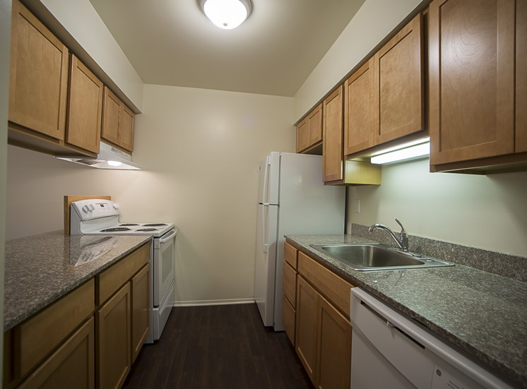 Birch cabinets fill the kitchen with plenty of storage at Woodland Villa Apartments in Westland, MI