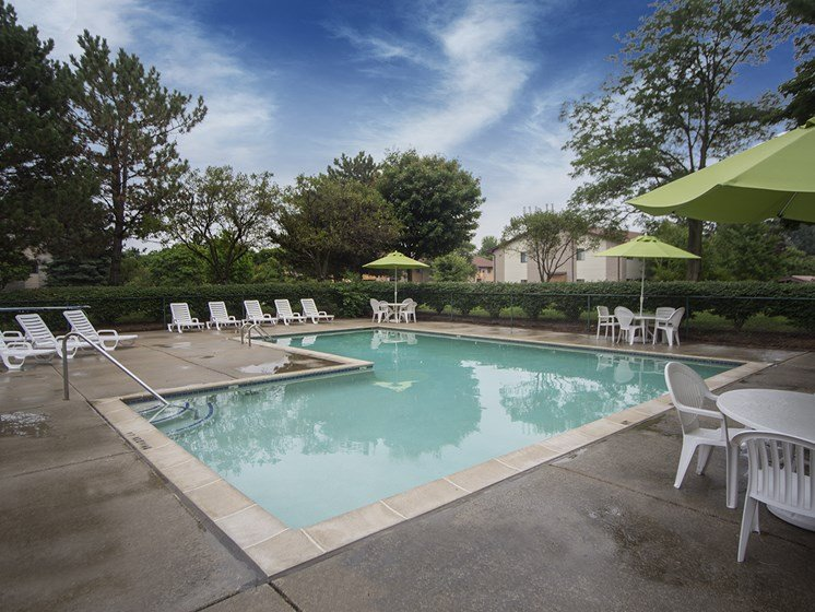 Heated pool (open April through October) with large sun deck at Woodland Villa Apartments in Michigan 48185