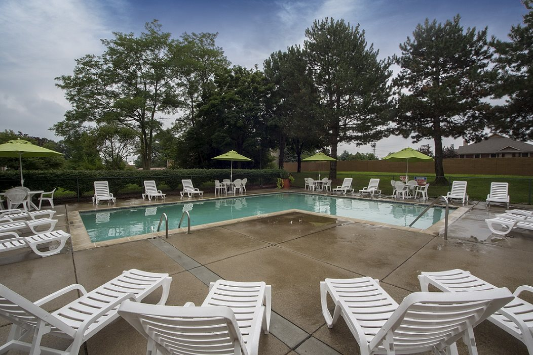 Heated pool (open April through October) with large sun deck at Woodland Villa Apartments in Michigan