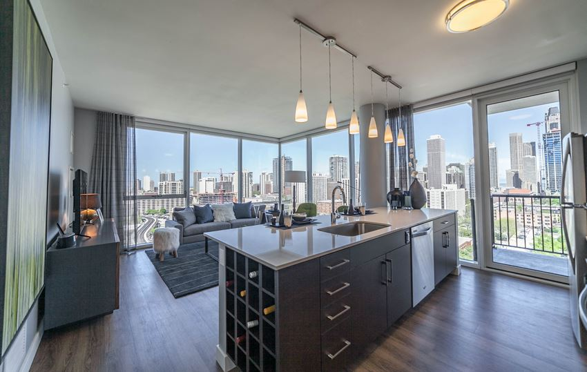 One bedroom kitchen with built-in wine rack, stainless steel appliances, cherry cabinets and hardwood flooring with floor to ceiling wrap around windows in the living room