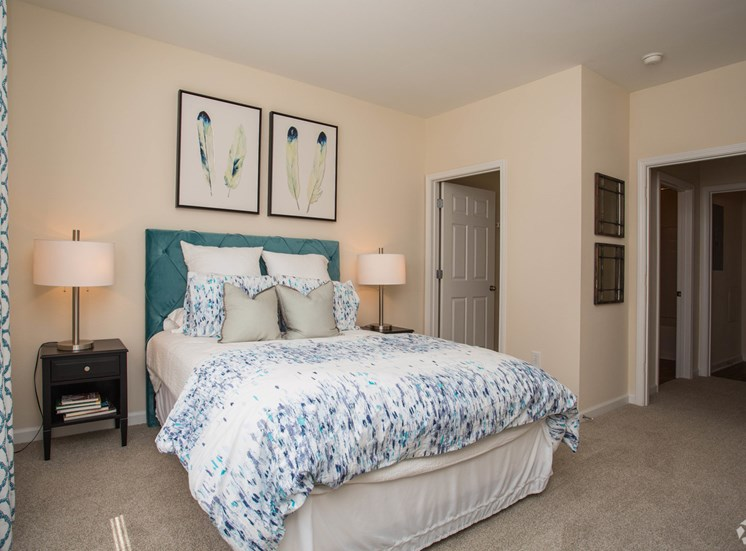 A bed, bathroom and closet are closely connected in a comfy bedroom at The Apartments at the Venue near LaGrange, GA.