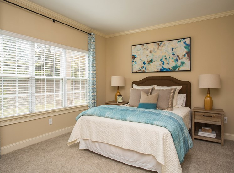 Daylight shines through the large, three windows in a  bedroom at The Apartments at the Venue near LaGrange, GA.