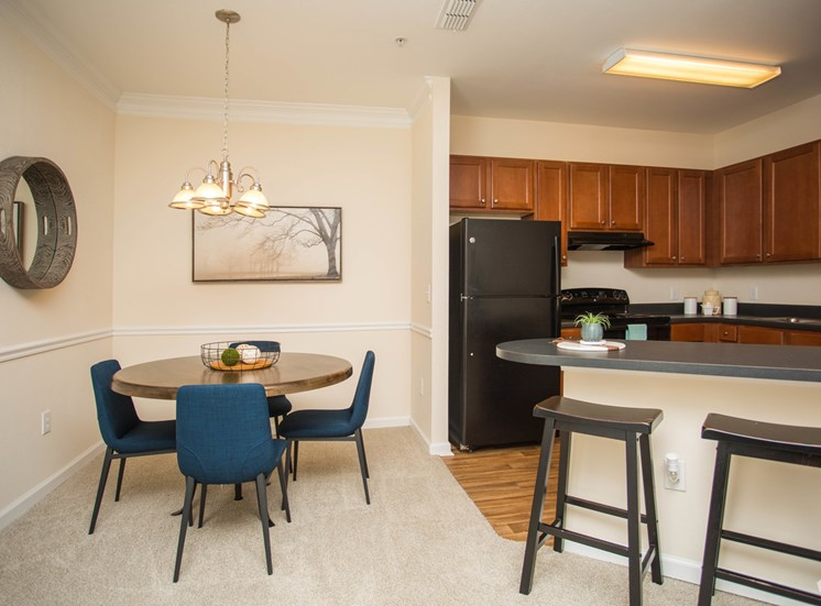A dining room area leads to a hard-floored kitchen with wood cabinets at The Apartments at the Venue near LaGrange, GA.
