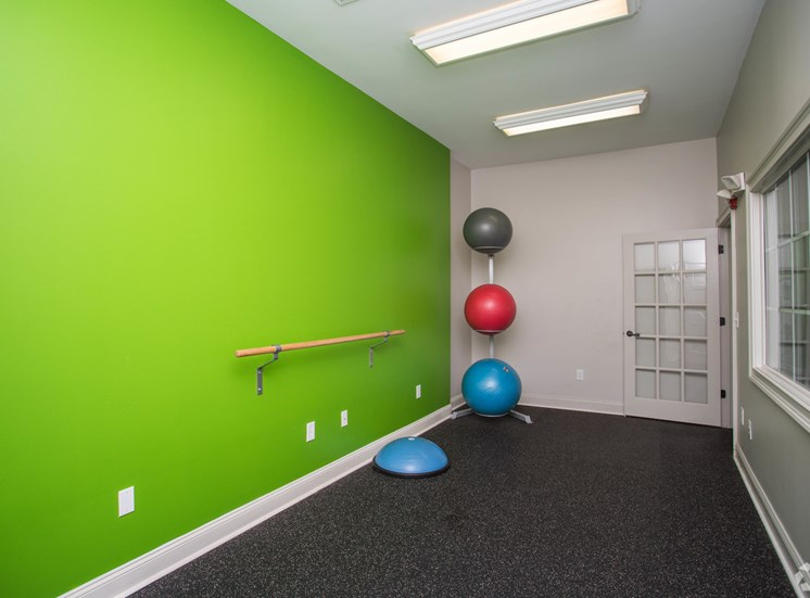 A mounted bar and set of yoga balls rest in the fitness center at The Apartments at the Venue near LaGrange, GA.