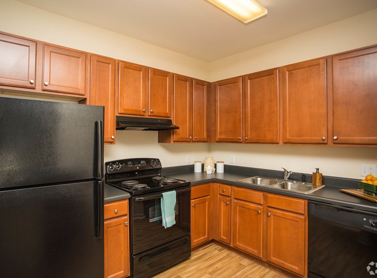 Wood cabinets surround modern black appliances in a kitchen at The Apartments at the Venue near LaGrange, GA.