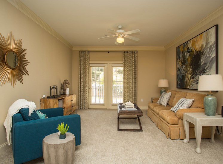A couch, midcentury modern chair and furnishings make up a living room at The Apartments at the Venue near LaGrange, GA.