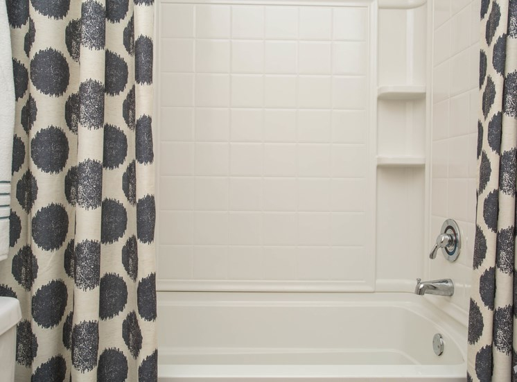 Spotless tiling and black-and-white patterned curtains make up the shower The Apartments at the Venue near LaGrange, GA.