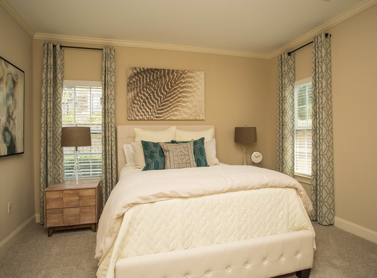 A large, elevated bed  sits between two windows in a bedroom at The Apartments at the Venue near LaGrange, GA.