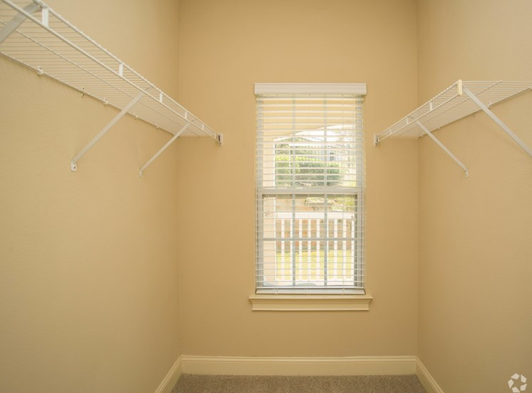 Wire shelves hang high in a large closet space with window at The Apartments at the Venue near LaGrange, GA.