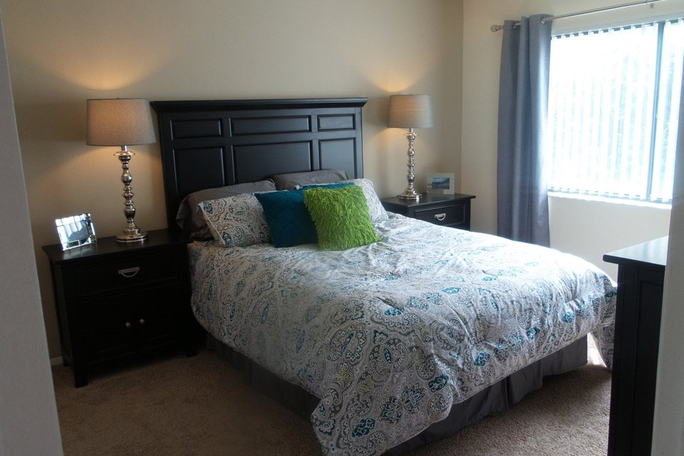 Spacious bedroom with bed, nightstands and large window | Bay Club Apartments