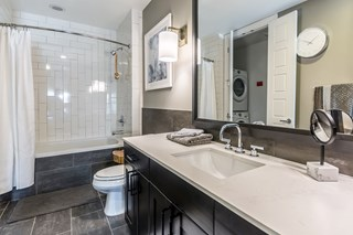 large apartment bathroom with grey tile interior