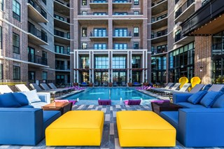 bright outdoor furniture next to large outdoor swimming pool at apartment complex near deep ellum