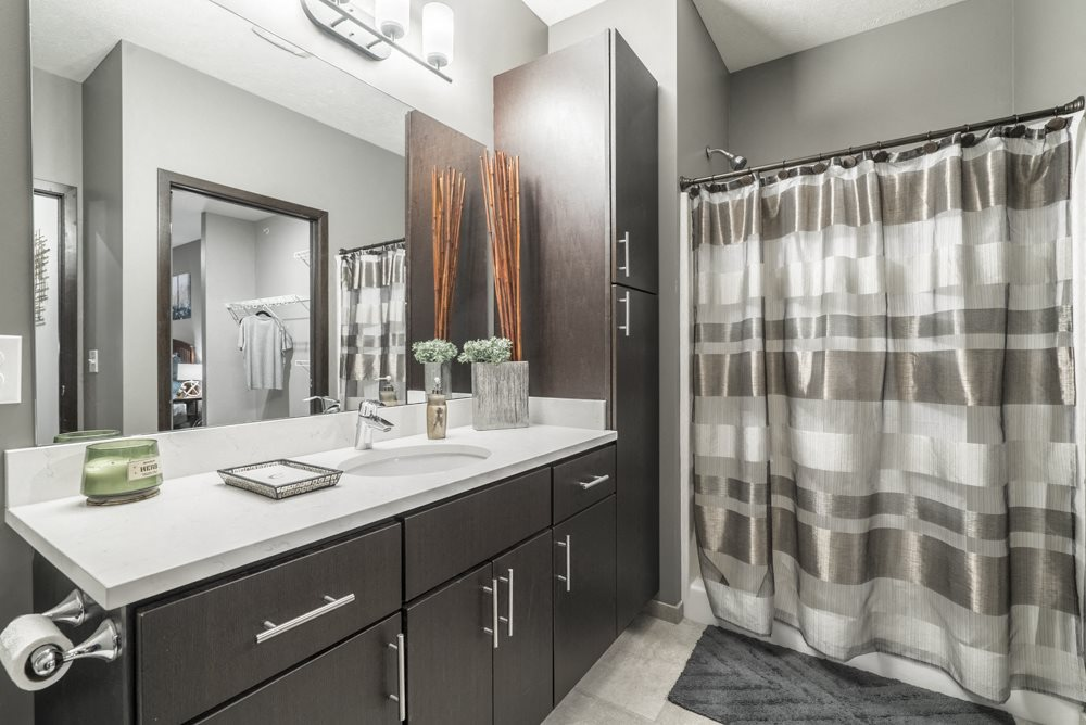 Bathroom with dark cabinetry and quartz countertops at The Conrad in midtown Omaha NE