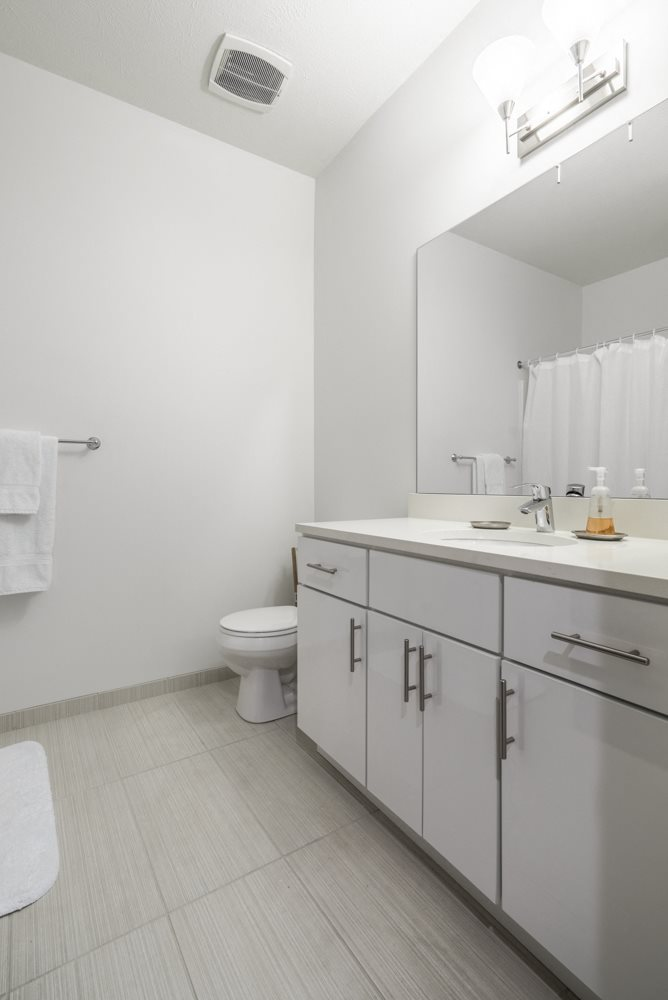 Contemporary bathroom with white cabinetry and white quartz countertops at The Conrad apartments