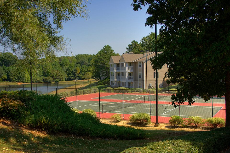 Two well-lit tennis courts to play on day or night at Lakeside at Arbor Place Apartments in Douglasville, GA