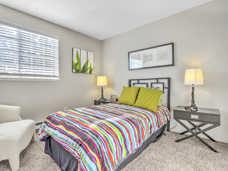 One, Two and Three Bedroom Apartments in Renton WA - The Windsor Apartments Bedroom with Plush Carpeting, Twin Bed, and Chic Modern Decor