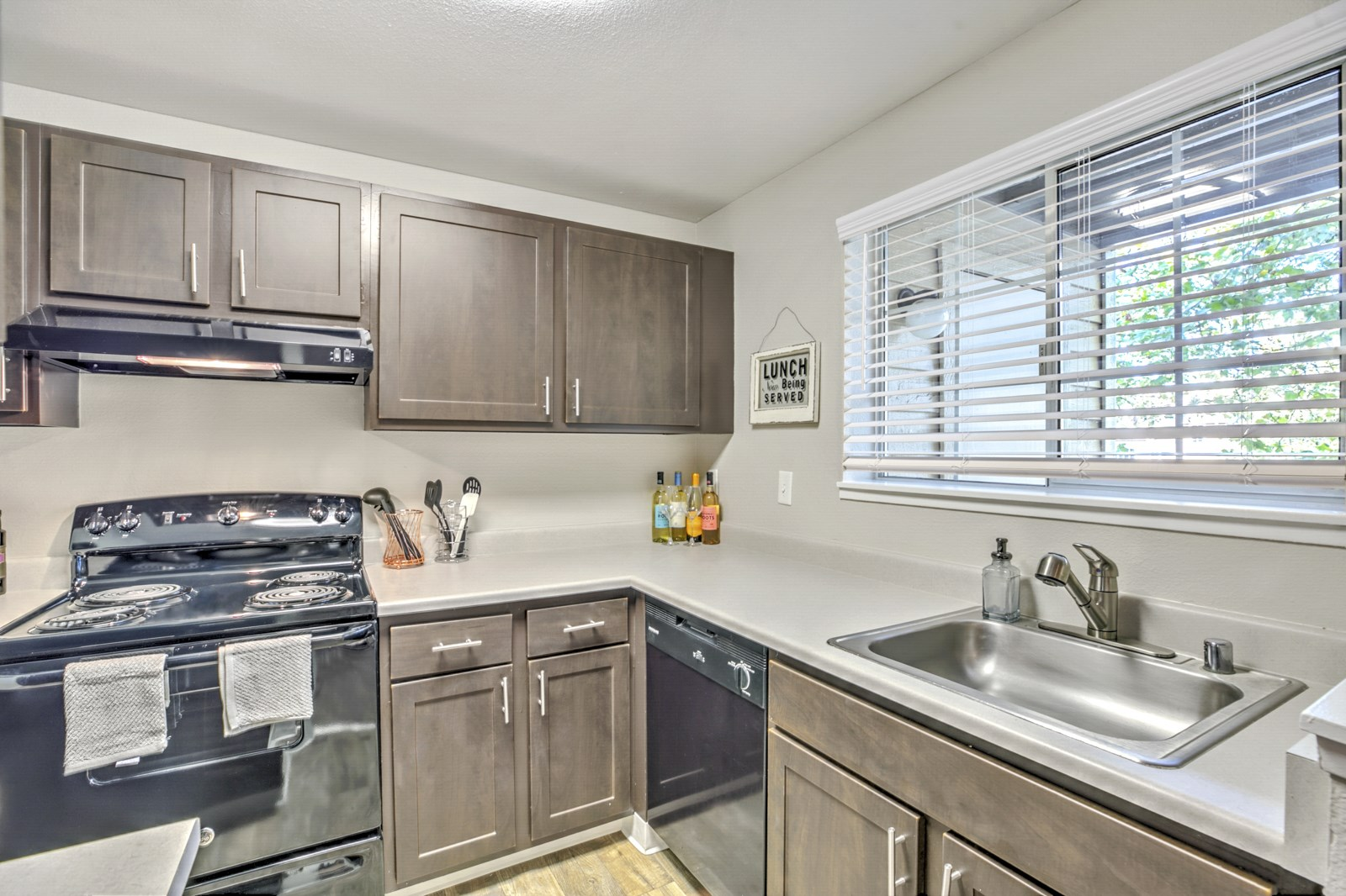 Renton WA Apartments - The Windsor Apartments Kitchen With Black Appliances, Stainless Steel Sink and Sleek Cabinets and Countertops