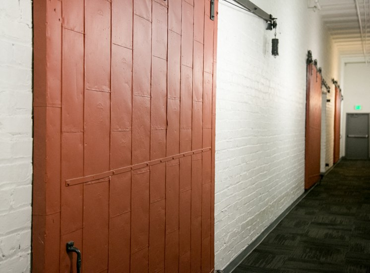 red warehouse doors and white walls in fix play hallway