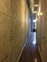 Apartment entrance with exposed brick and hardwood floors in Fix Play Lofts in Birmingham, AL 35203