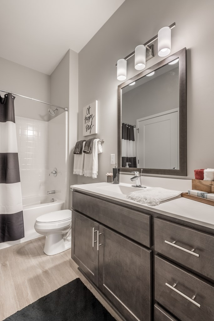 Interiors- Bathroom with dark cabinets and white, cultured-marble countertops at The Preserve at Normandale Lake