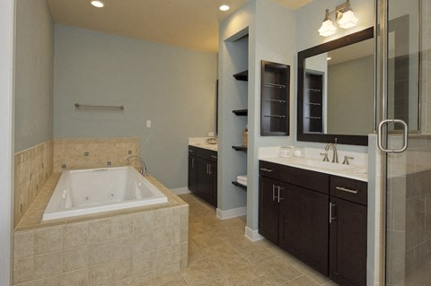 Large master bathroom with shower and spa bathtub at The Flats at Tioga Town Center