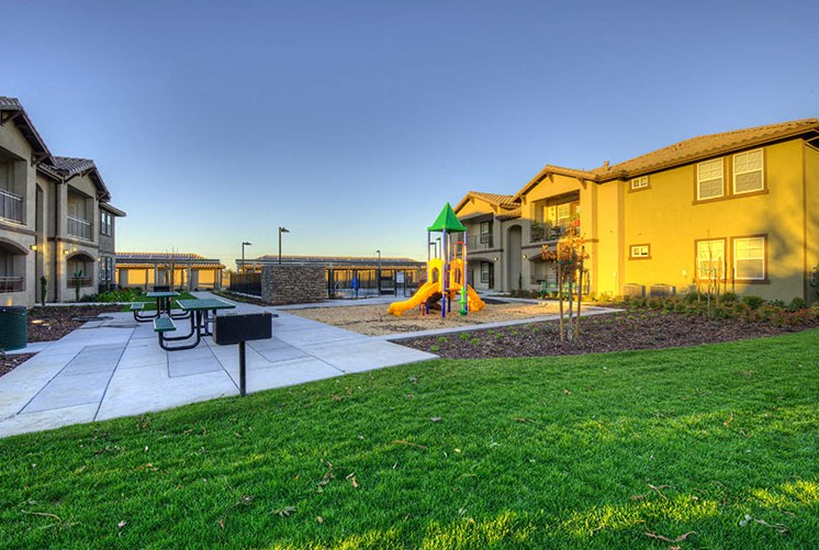 Ripon, CA Apartments for Rent - Luxe Ripon Bench and Playground Area