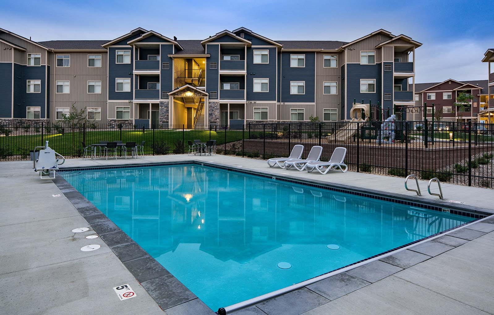 Pool with lounge chairs and apt buildings Colorado Springs, CO 80908 | Copper Range Apartment Homes